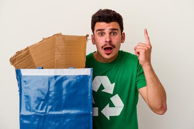 Young caucasian man recyclage carton isolé sur fond blanc