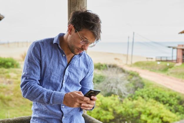 Young caucasian man textos sur son téléphone intelligent appuyé contre une balustrade en bois sur la terrasse de la cabane de plage.