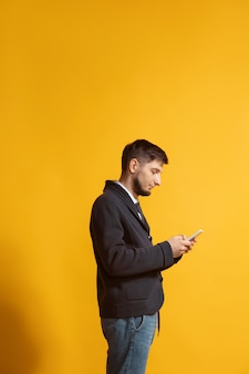 Young caucasian man using smartphone portrait de tout le corps sur jaune
