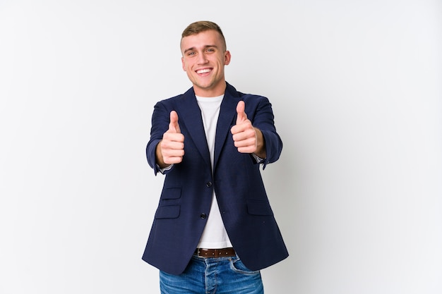 Young caucasian man with thumbs ups, cheers about something, support and respect concept.