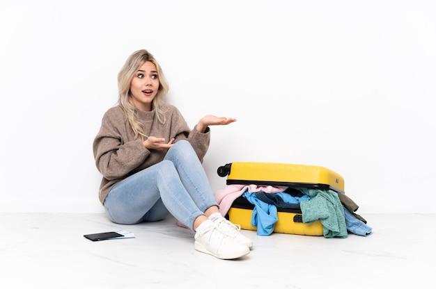 Young caucasian travel woman over assis sur le sol