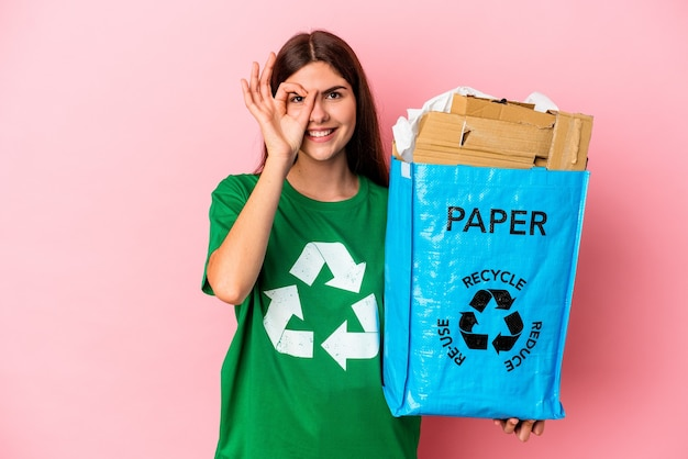 Young caucasian woman carton recyclé isolé sur mur rose excité en gardant le geste ok sur les yeux
