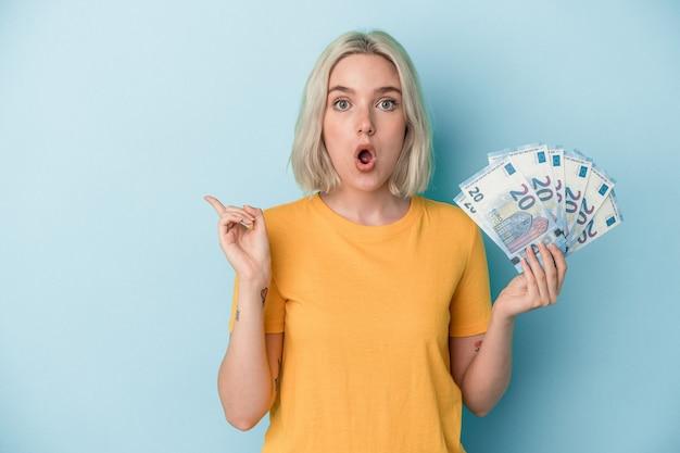 Young caucasian woman holding bills isolé sur fond bleu pointant vers le côté
