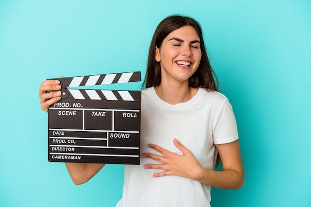 Young caucasian woman holding a clap isolated on blue wall rit bruyamment en gardant la main sur la poitrine