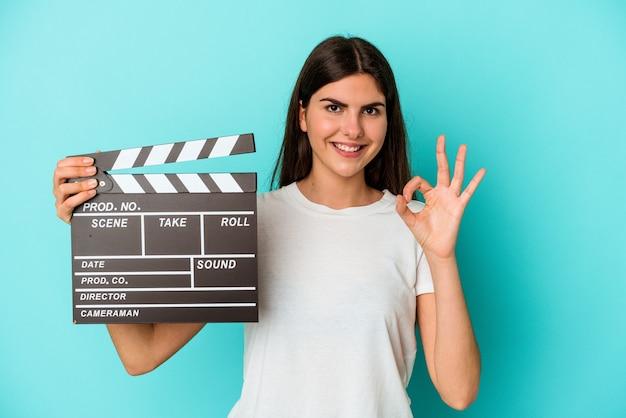 Young caucasian woman holding a clap isolé sur mur bleu joyeux et confiant montrant le geste ok