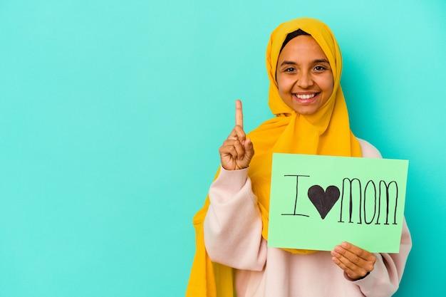 Young caucasian woman holding a j'aime maman isolé sur un mur rose montrant le numéro un avec le doigt