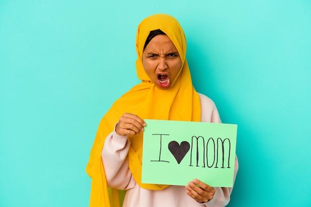 Young caucasian woman holding a j'aime maman isolée sur un mur rose hurlant très en colère et agressif.