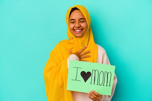 Young caucasian woman holding a j'aime maman isolée sur le mur rose rit bruyamment en gardant la main sur la poitrine