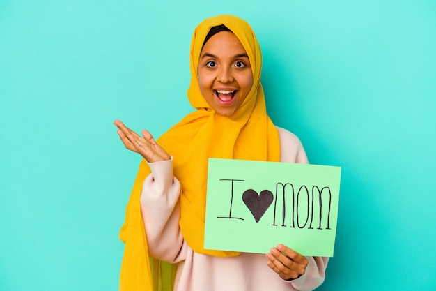 Young caucasian woman holding a j'aime maman isolée sur un mur rose surpris et choqué