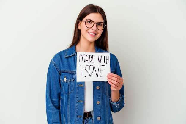 Young caucasian woman holding a made with love placard isolé sur un mur blanc montrant un espace de copie sur une paume et tenant une autre main sur la taille