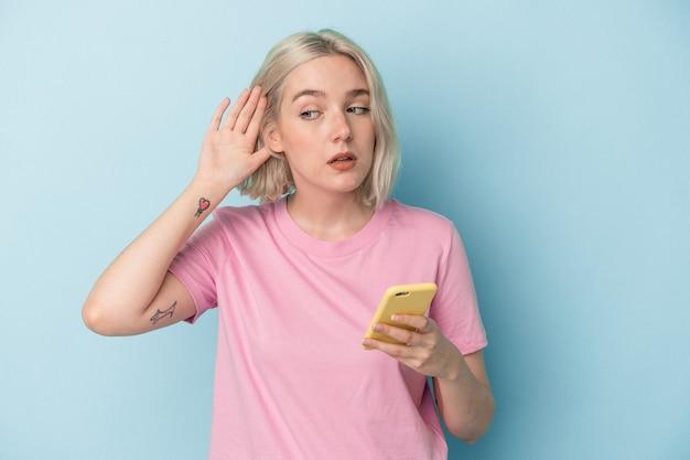 Young caucasian woman holding mobile phone isolé sur fond bleu essayant d'écouter un potin.