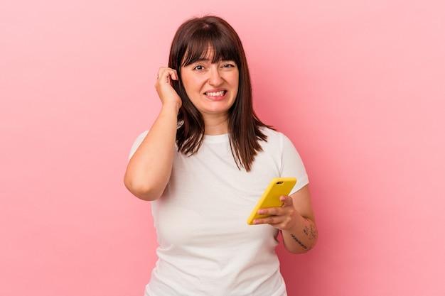 Young caucasian woman holding mobile phone isolé sur fond rose couvrant les oreilles avec les mains.