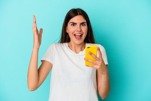 Young caucasian woman holding a mobile phone isolé sur un mur bleu recevant une agréable surprise, excité et levant les mains