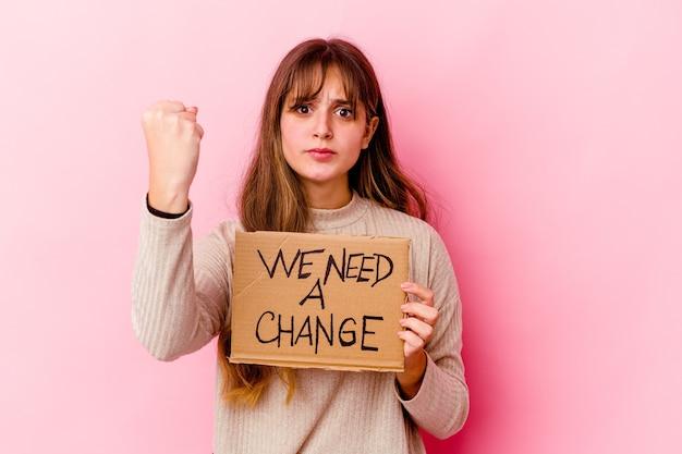 Young caucasian woman holding a nous avons besoin d'une pancarte de changement isolée montrant le poing à la caméra, expression faciale agressive.