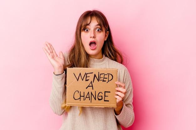 Young caucasian woman holding a nous avons besoin d'une pancarte de changement surpris et choqué.