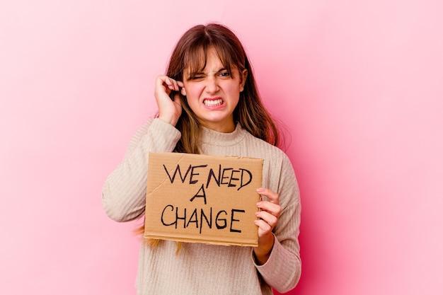Young caucasian woman holding a nous avons besoin d'une plaque de changement isolé couvrant les oreilles avec les mains.