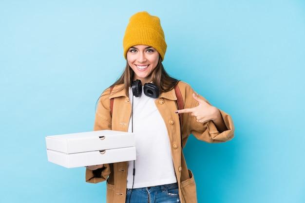 Young caucasian woman holding pizzas personne isolée pointant à la main vers un espace de copie de chemise