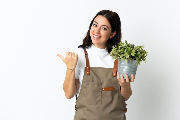 Young caucasian woman holding a plant isolé sur fond blanc pointant vers le côté pour présenter un produit
