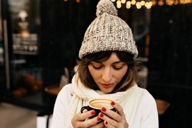 Young caucasian woman in bonnet tricoté, boire du café et marcher dans les rues dans les lumières de noël
