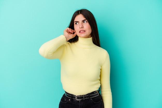 Young caucasian woman isolated on blue wall couvrant les oreilles avec les doigts, stressé et désespéré par un bruit ambiant