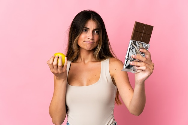 Young caucasian woman isolated on pink ayant des doutes tout en prenant une tablette de chocolat dans une main et une pomme dans l'autre