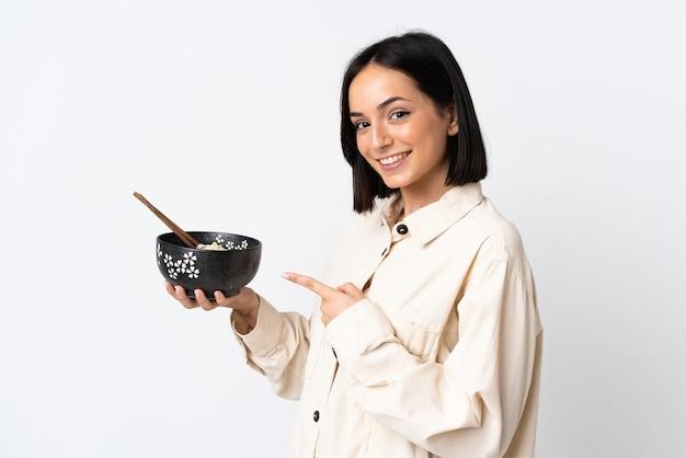 Young caucasian woman isolated on white wall et le pointant tout en tenant un bol de nouilles avec des baguettes