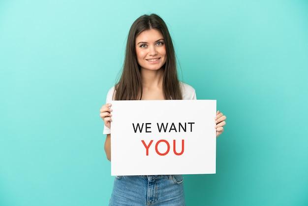 Young caucasian woman isolé sur fond bleu holding we want you board avec une expression heureuse