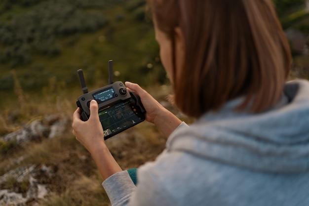 Young caucasian woman la navigation d'un drone volant avec télécommande