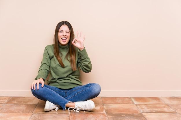 Young caucasian woman sitting on the floor isolated fait un clin d'œil et tient un geste correct avec la main
