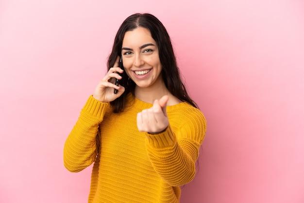 Young caucasian woman using mobile phone isolé sur fond rose faisant le geste de l'argent