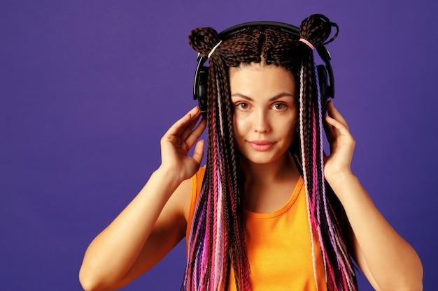 Young caucasian woman with african cornrows écouter de la musique avec des écouteurs contre le violet