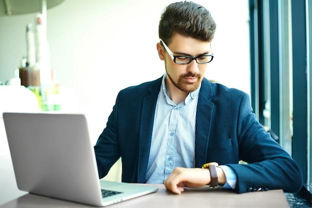 Young fashion smiling hipster man dans le café de la ville pendant l'heure du déjeuner avec un ordinateur portable en costume en regardant les montres