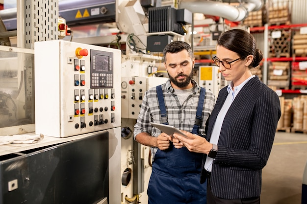Young female business partner in formalwear scrolling in tablet lors de la recherche de données techniques avec ingénieur debout à proximité