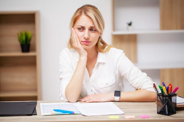 Young female business woman sent un mal de dents dans son bureau