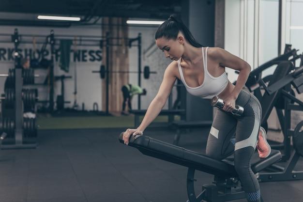 Young fit femme sportswear exerçant avec des haltères au gymnase, espace copie