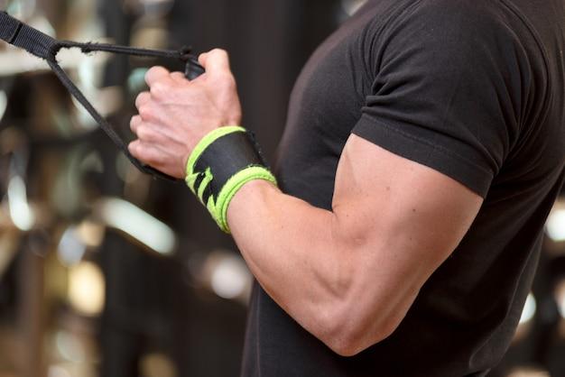 Young fit homme musclé se bouchent faire des triceps abaisser exercice de corde extension dans un centre de remise en forme moderne.