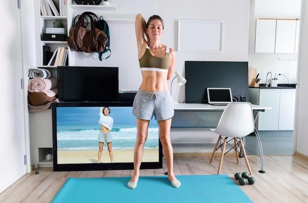 Young fit woman doing yoga stretching exercice intérieur près de l'écran du téléviseur sur l'isolement à son domicile
