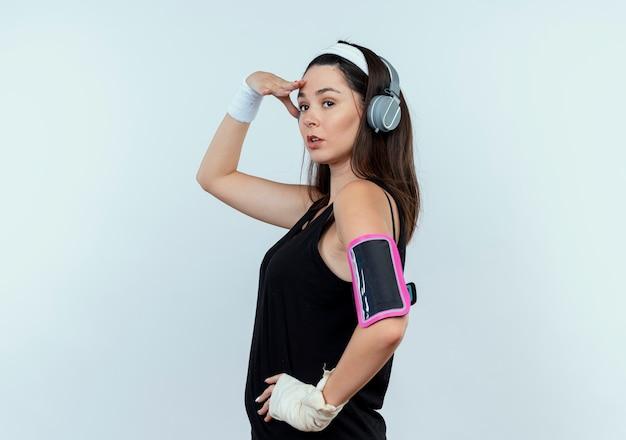 Young fitness woman in headband avec casque et brassard smartphone à la recherche de loin avec la main sur la tête debout sur un mur blanc