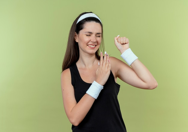 Young fitness woman in headband serrant le poing avec les yeux fermés avec une expression agacée debout sur un mur léger