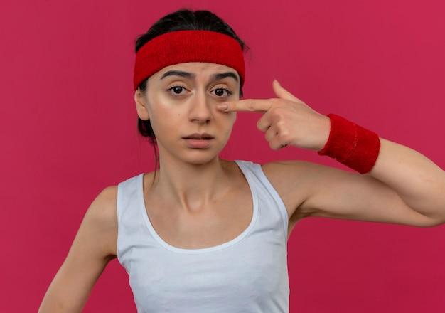 Young fitness woman in sportswear avec bandeau confus pointant avec l'index sur son nez debout sur un mur rose