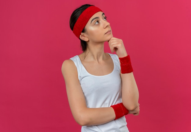 Young fitness woman in sportswear avec bandeau à côté de la pensée perplexe debout sur le mur rose