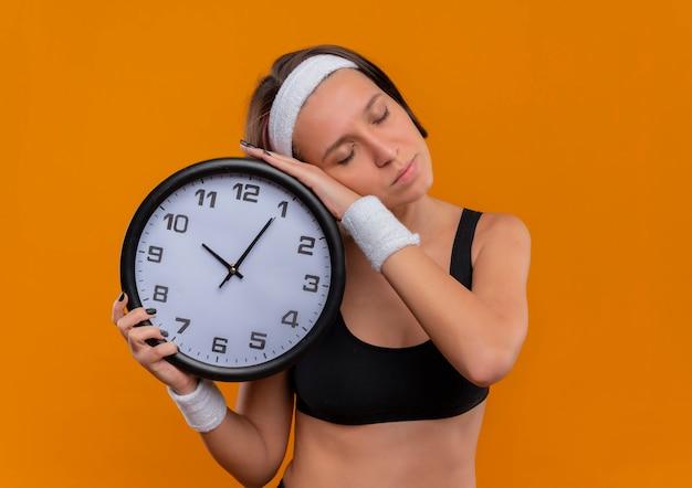 Young fitness woman in sportswear avec bandeau hugging horloge murale se penchant la tête dessus avec les yeux fermés debout sur le mur orange
