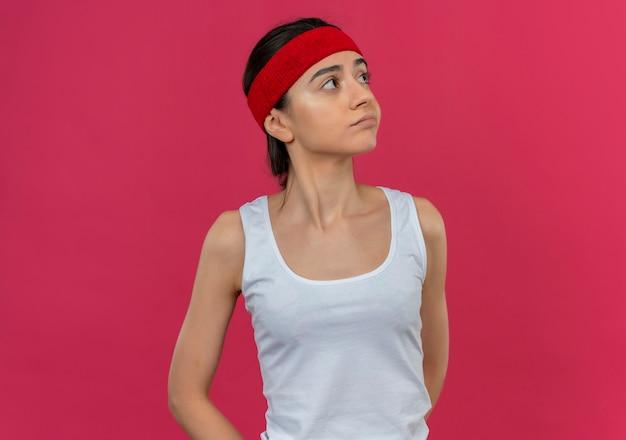 Young fitness woman in sportswear avec bandeau, regardant de côté avec une expression sceptique debout sur un mur rose