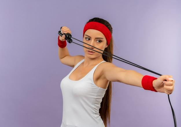 Young fitness woman in sportswear avec bandeau tenant la corde à sauter comme visant avec un arc et une flèche debout sur un mur gris