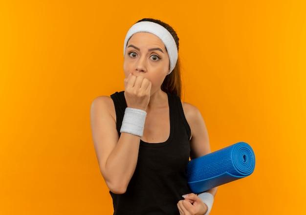 Young fitness woman in sportswear avec bandeau tenant un tapis de yoga choqué couvrant la bouche avec la main debout sur le mur orange