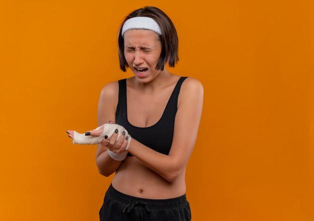 Young fitness woman in sportswear avec bandeau touchant son poignet à la souffrance souffrant de douleur debout sur un mur orange
