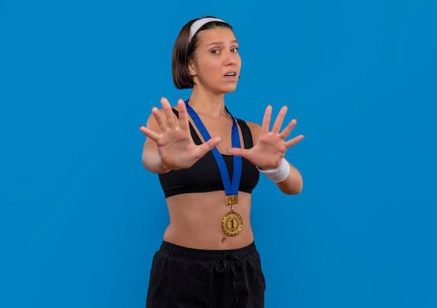 Young fitness woman in sportswear avec médaille d'or autour de son cou faisant le geste de défense avec les mains peur debout sur le mur bleu