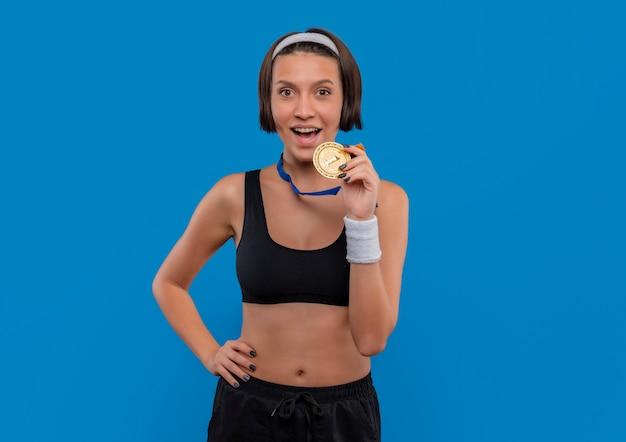Young fitness woman in sportswear avec médaille d'or autour de son cou heureux et sorti debout sur le mur bleu