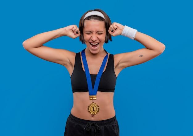 Young fitness woman in sportswear avec médaille d'or autour de son cou serrant les poings se réjouissant de son succès debout sur le mur bleu