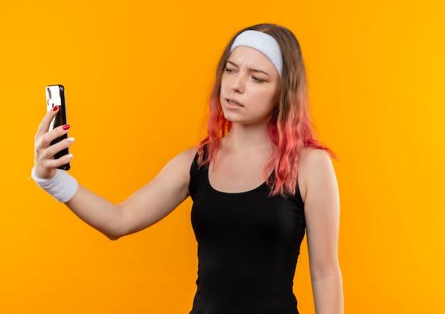 Young fitness woman in sportswear prenant selfie à l'aide de smartphone avec visage sérieux debout sur un mur orange